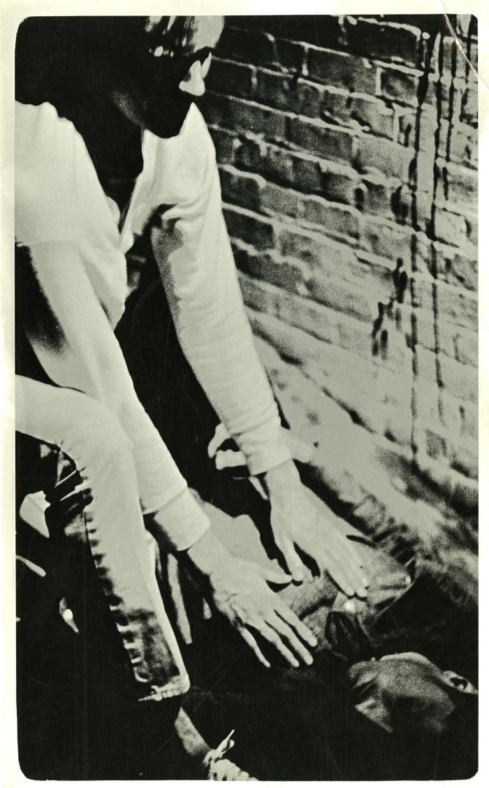 Photograph of two figures against a brick wall